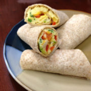 whole wheat burritos filled with egg and red and green pepper cut on a plate