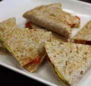whole wheat breakfast quesadilla toasted and cut in triangle and placed on a while plate